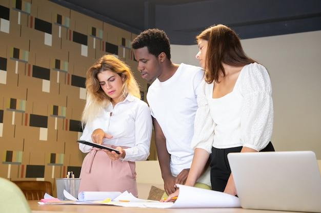 Diseñadores multiétnicos mirando la pantalla de la tableta en manos de mujer