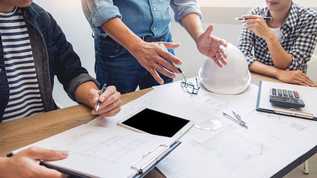 Los diseñadores de la oficina están trabajando discusión el arquitecto de planos en un nuevo proyecto diseño dibuje el trabajo en equipo en un escritorio de madera.