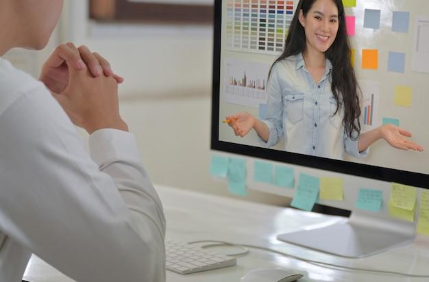 Diseñadores profesionales masculinos y femeninos que cumplen la planificación con videoconferencia.