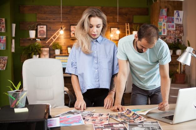 Diseñadores que trabajan juntos en un escritorio en una oficina moderna para crear una línea de vestimenta de moda.