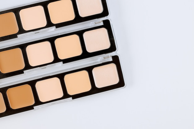 Diseñe hermosos colores de la paleta de sombras de ojos de maquillaje en una superficie blanca aislada
