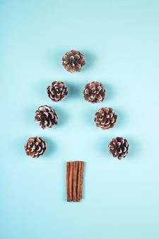 Diseño de árbol de navidad de conos y canela en rama azul