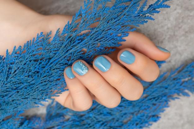Diseño de uñas azul. mano femenina cuidada