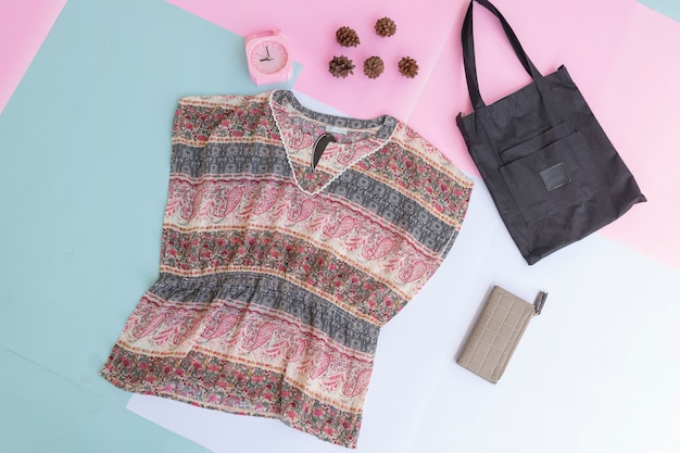 Diseño de base de ropa de mujer, exterior sobre fondo pastel menta pálido. concepto de estilo de vida. despertador. bolsa pequeña. bolso
