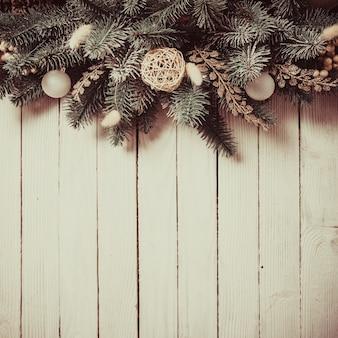 Diseño de borde navideño con pinos y adornos blancos.