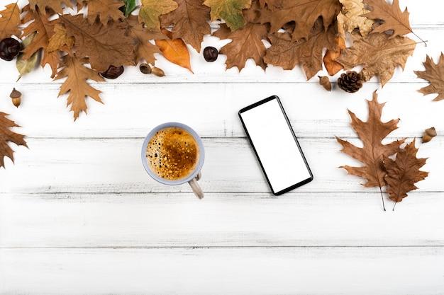 Diseño de café y teléfono inteligente en el fondo de las hojas