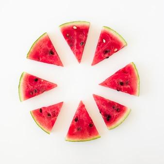 Diseño circular hecho con rodajas de sandía triangular sobre fondo blanco