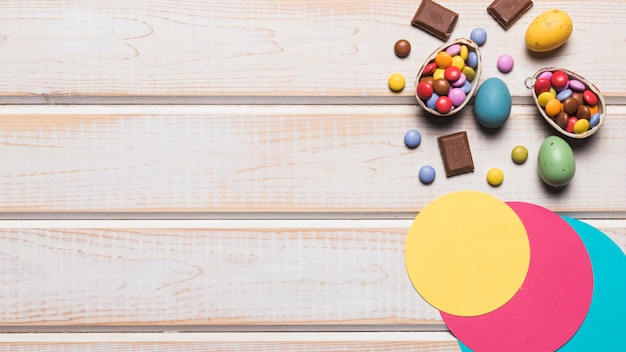 Diseño de círculo de papel; huevos de pascua coloridos y caramelos de gemas en el escritorio de madera