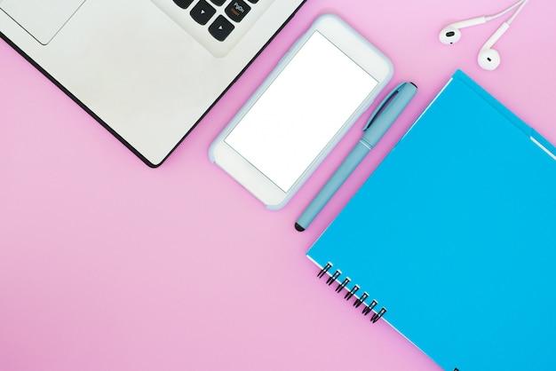 Diseño con una computadora portátil, teléfono, bloc de notas y auriculares sobre un fondo rosa. lugar para el texto. flat lay cosas para trabajar