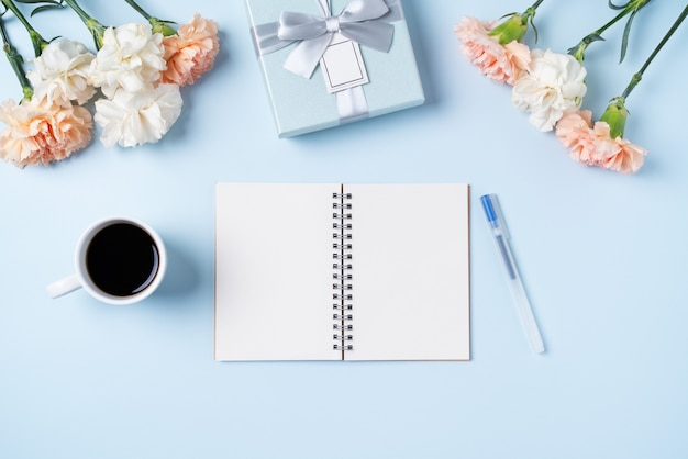 Diseño concpet del saludo del día de la madre con flor de clavel, idea de regalo de vacaciones y diario de cuaderno en el fondo del escritorio de la madre.