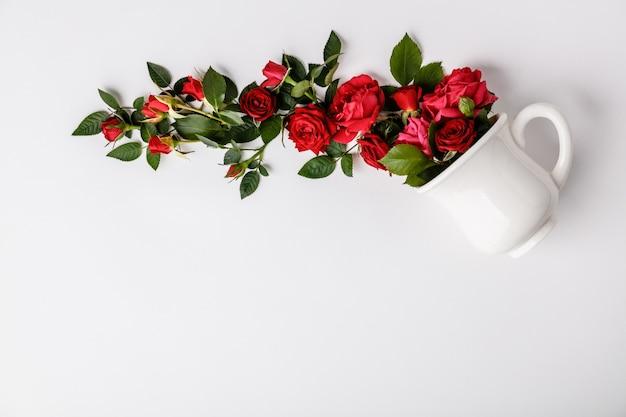Diseño creativo hecho de café o taza de té con rosas rojas sobre fondo blanco.