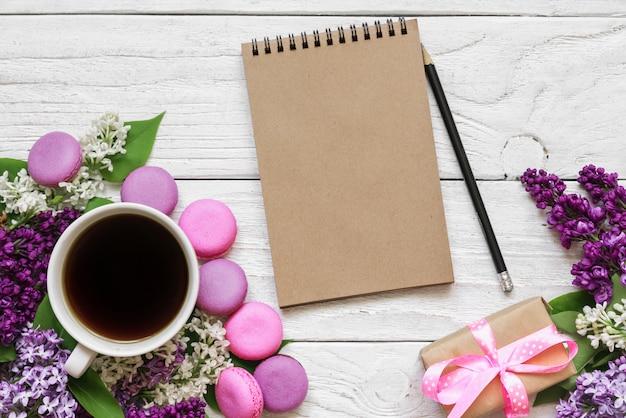 Diseño creativo hecho con flores de color lila, cuaderno de papel en blanco, taza de café y macarrones en la mesa de madera blanca