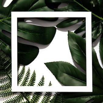 Diseño creativo hecho de hojas tropicales con marco vacío de papel blanco.