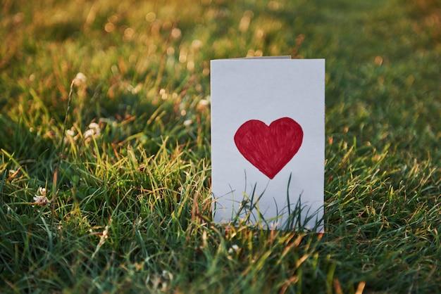 Diseño creativo de hierba verde con una tarjeta de papel.