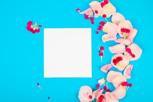 Diseño creativo con pétalos de rosa sobre un espacio azul. tarjeta en blanco. copiar espacio para texto.