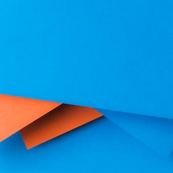 Diseño creativo realizado con papel azul y naranja.