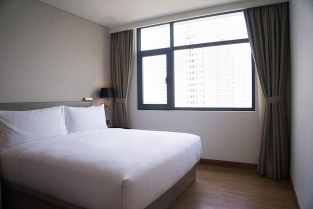 Diseño de dormitorio pequeño con cama doble, ropa blanca y ventana.