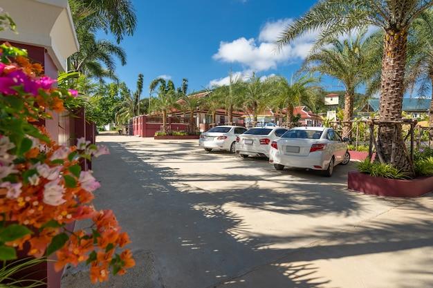 El diseño exterior de la casa, la casa cuenta con autos blancos en el estacionamiento al aire libre con cielo azul y árbol verde