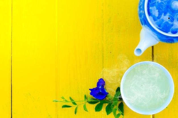 Diseño floral caliente de la taza y de la tetera de té en el fondo amarillo, hora del descanso del té