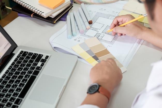 Diseño gráfico y muestras de color y bolígrafos sobre un escritorio. dibujo arquitectónico con herramientas de trabajo y accesorios.