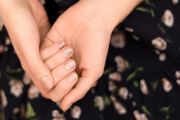 Diseño de uñas gris. mano femenina con manicura brillo.