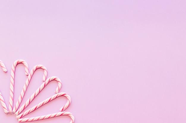 Diseño hecho con bastón de caramelo de navidad en la esquina de fondo rosa