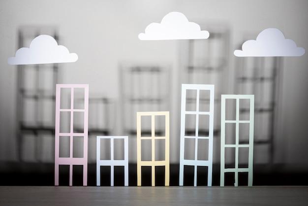 Diseño inmobiliario con edificios de papel y nubes.