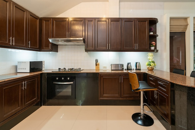 El diseño interior de la casa, el hogar, la villa y el apartamento cuenta con encimera de madera, taburete, campana extractora, horno, microondas y gabinete