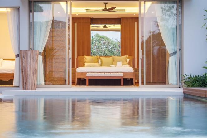 Diseño interior de lujo en el dormitorio de la villa con piscina y cama extragrande