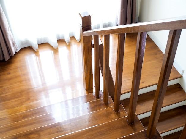 Diseño interior con escaleras y cortinas marrones, arriba y abajo con escalera y escalera de madera.