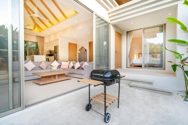 Diseño interior y exterior en dormitorio de villa con piscina.