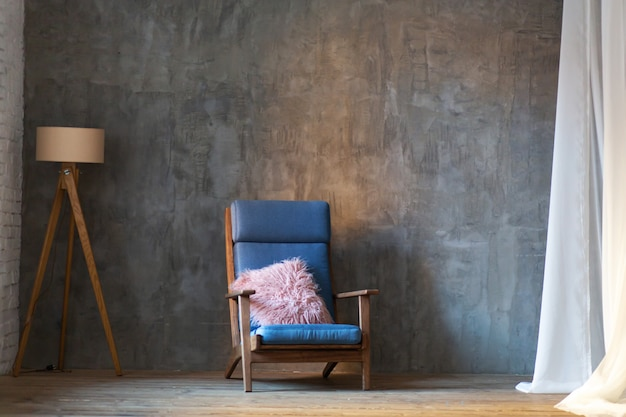Diseño interior minimalista. sillón y lámpara sobre fondo de pared