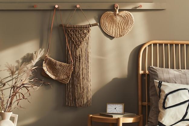 Diseño interior moderno de dormitorio elegante con decoración, macramé neutro, perchero, flor seca, canasta, hermosas sábanas, manta, almohadas y accesorios personales.