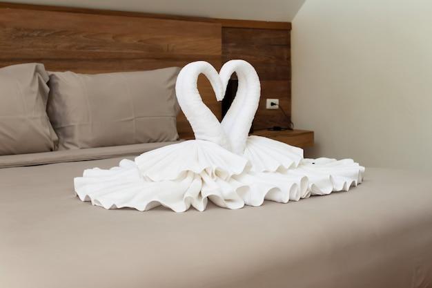 Diseño de interiores de dormitorio con cisnes de la decoración de toallas en la cama