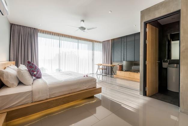 Diseño de interiores en dormitorio moderno de villa de piscina con iluminación.