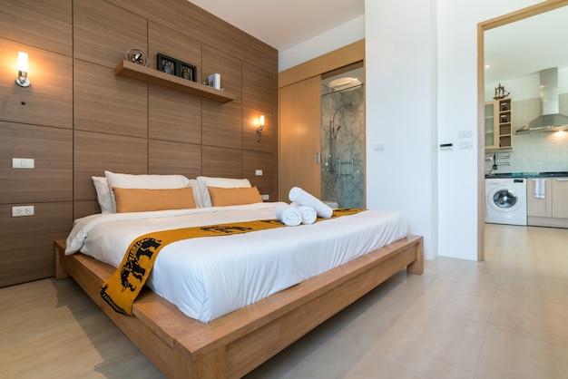 Diseño de interiores en el dormitorio de la villa de la piscina con acogedora cama king
