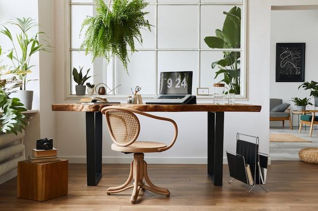 Diseño de interiores de espacio de oficina en casa con elegante escritorio de madera, hermosa silla, computadora portátil, platos, libros y elegantes accesorios personales en una acogedora decoración del hogar.