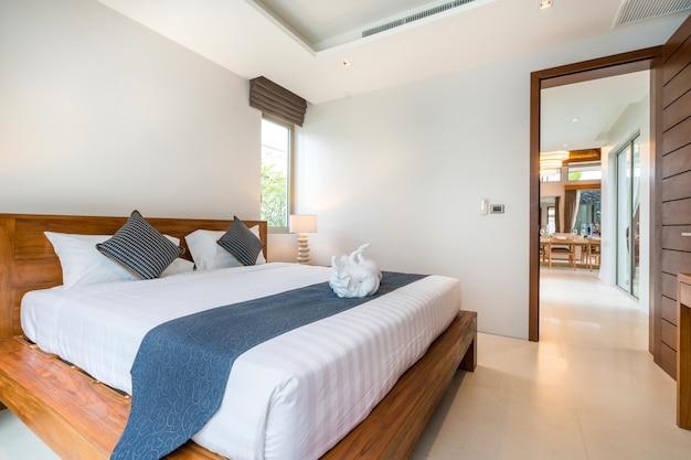 Diseño de interiores de lujo en el dormitorio de la villa de la piscina con una acogedora cama king size.