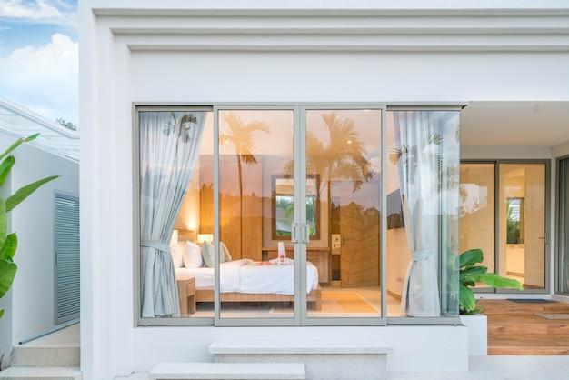 Diseño de interiores de lujo en el dormitorio de la villa de la piscina con techos altos y rosas en la cama en la casa o edificio de la casa