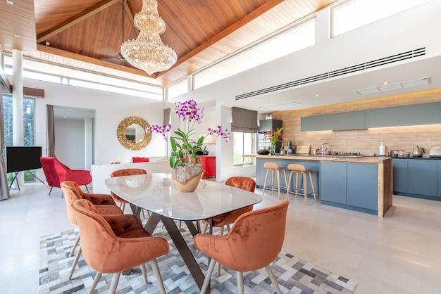 Diseño de interiores en sala y área de cocina abierta con mesa de comedor.