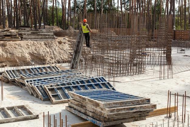 Diseño de jaula de refuerzo de refuerzo para casa de armazón de hormigón, casa de ladrillo, encofrado para vertido de hormigón, obra de construcción, grúa de trabajo, construcción de viviendas.