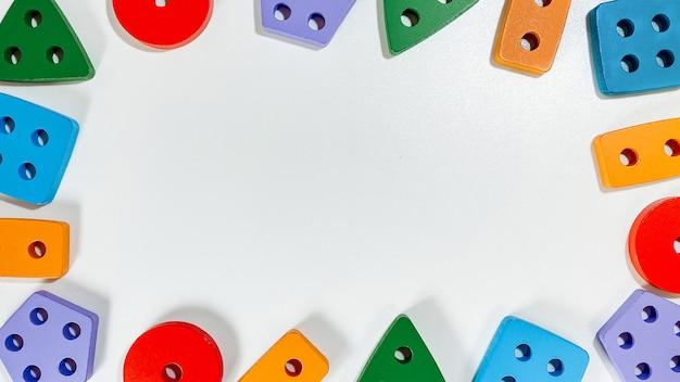 Un diseño de juguetes educativos para niños pequeños en forma de clasificadores multicolores sobre un fondo blanco.
