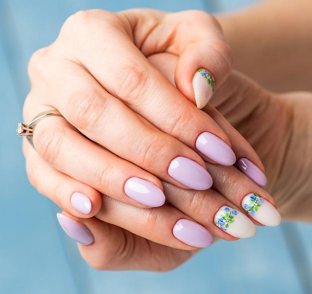 Diseño de uñas. manos con manicura blanca y lila brillante con flores de primavera. cerca de las manos femeninas. arte de uñas.