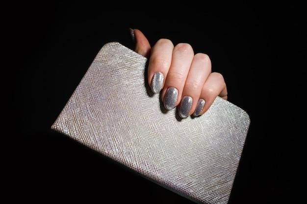 Diseño de uñas. manos con manicura de navidad plata brillante sobre fondo negro. cerca de las manos femeninas. arte de uñas.