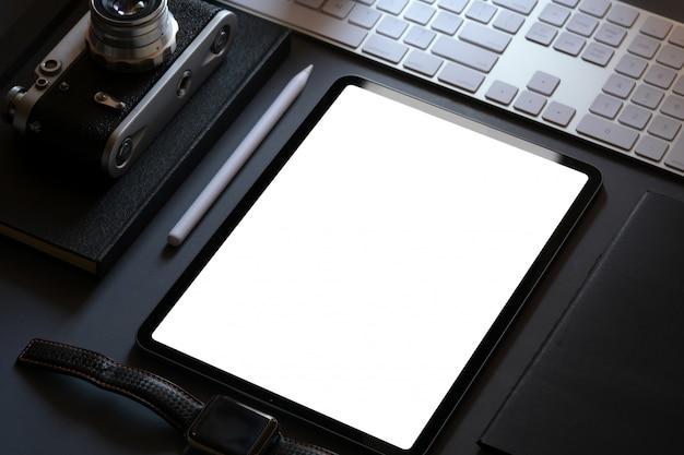 Diseño de maqueta corporativa de oficina con tableta de pantalla en blanco en el escritorio de cuero oscuro