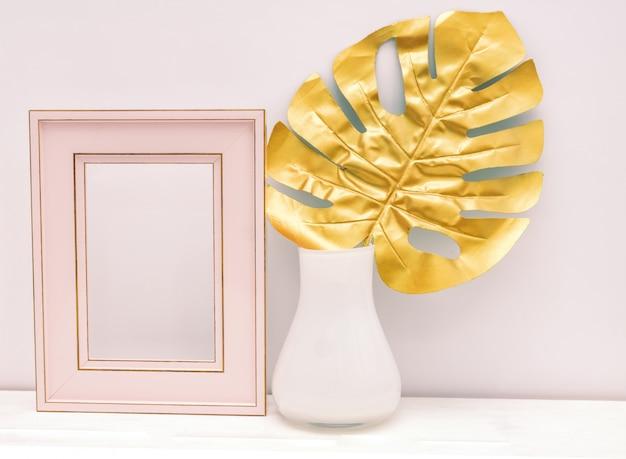 Diseño de maqueta interior dorado, rosa y blanco. vacie el photoframe y la hoja del monstera en el florero blanco en el fondo blanco de la pared. diseño de lujo de moda.