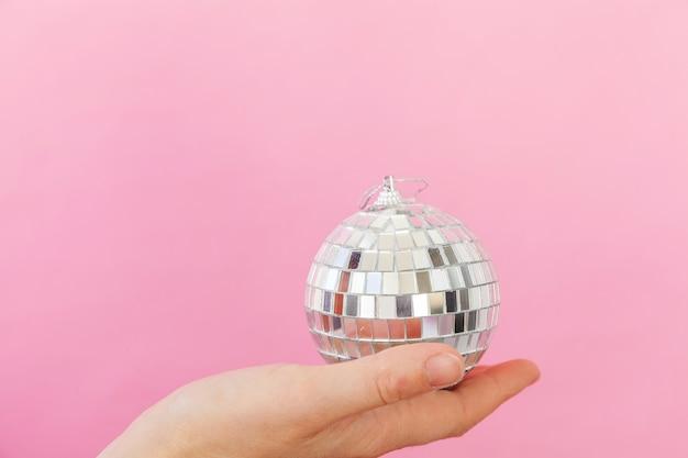 Diseño minimalista mano femenina mujer sosteniendo adorno de navidad bola de discoteca aislado en rosa pastel colorido de moda