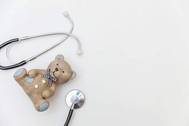Diseño minimalista oso de juguete y equipo de medicina estetoscopio aislado sobre fondo blanco. concepto de médico de niños de salud símbolo pediatra lay flat, vista superior copia espacio
