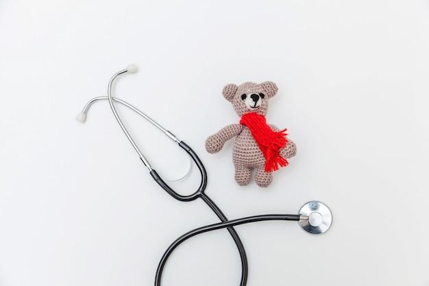 Diseño minimalista oso de juguete y equipo de medicina estetoscopio aislado