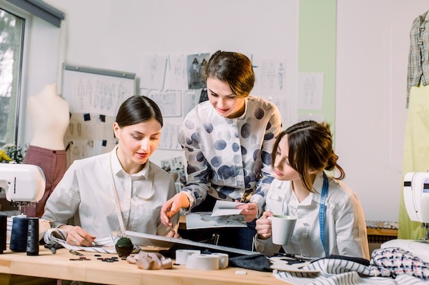 Diseño de moda, modista, sastre concept. tres jóvenes costureras caucásicas trabajando juntas en el luminoso taller, preparando una nueva colección de ropa hecha a mano.